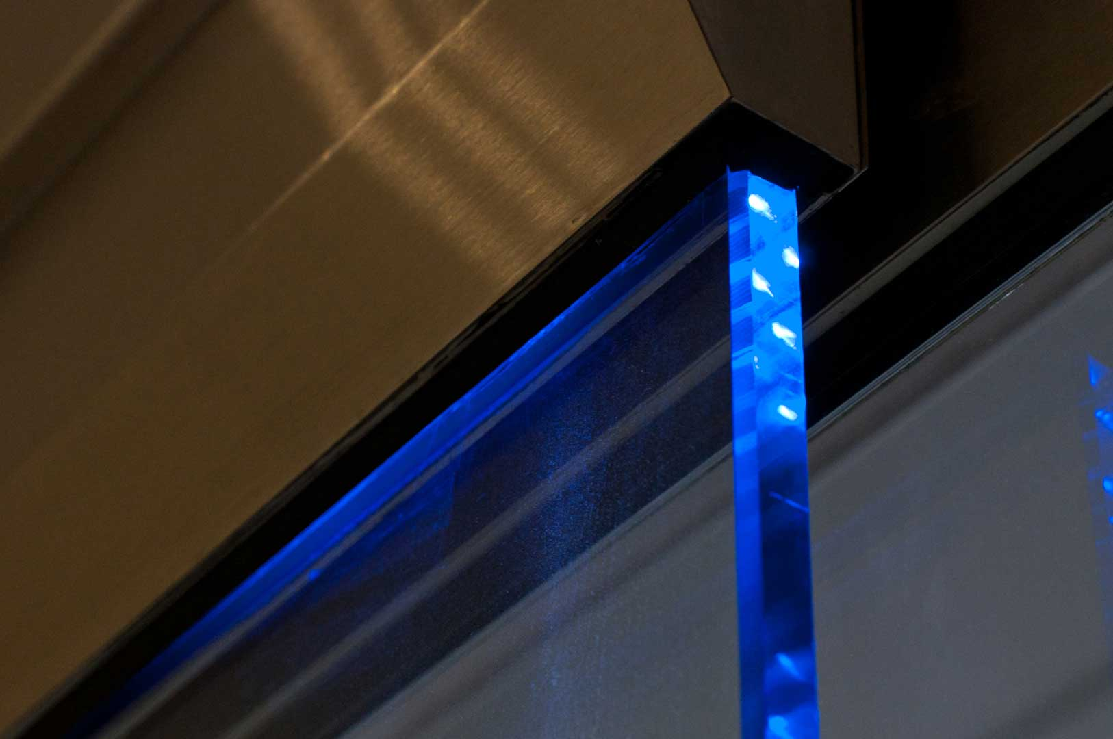 Blue lights shine through glass on Tormax sliding door system in Toronto installed by Explore1.ca