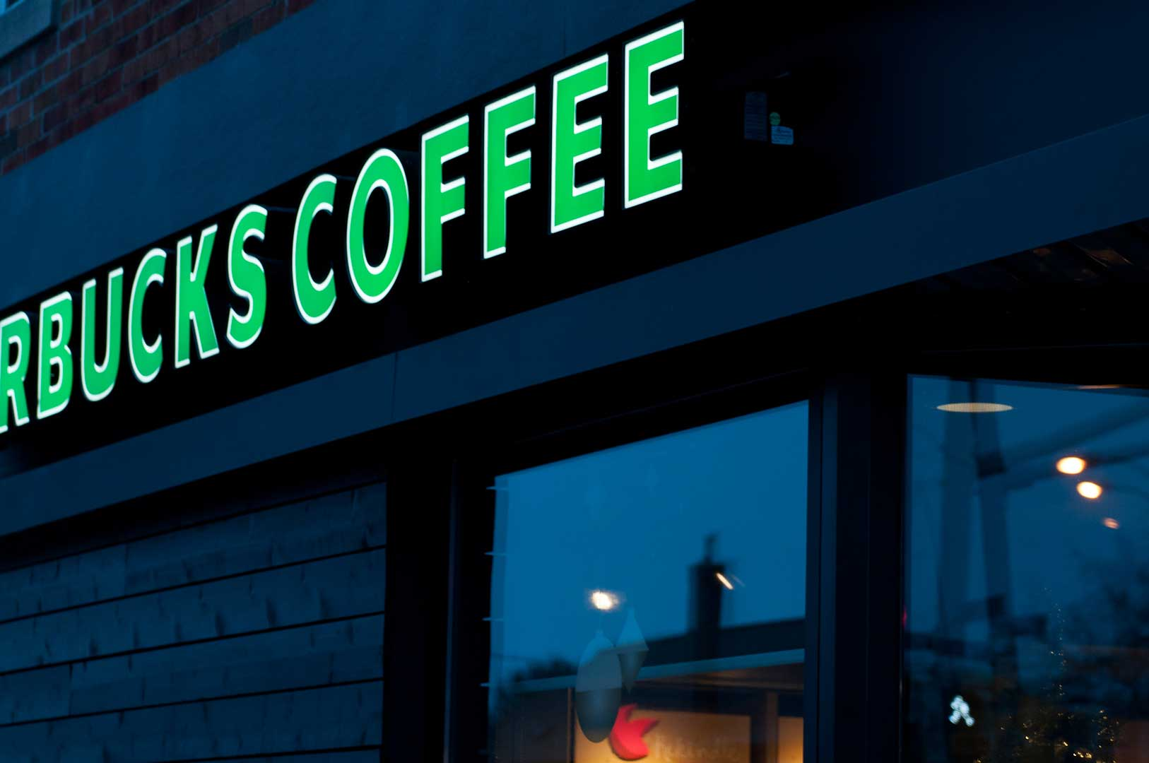 Dark Starbucks Sign Showing Metal Work by Explore1.ca