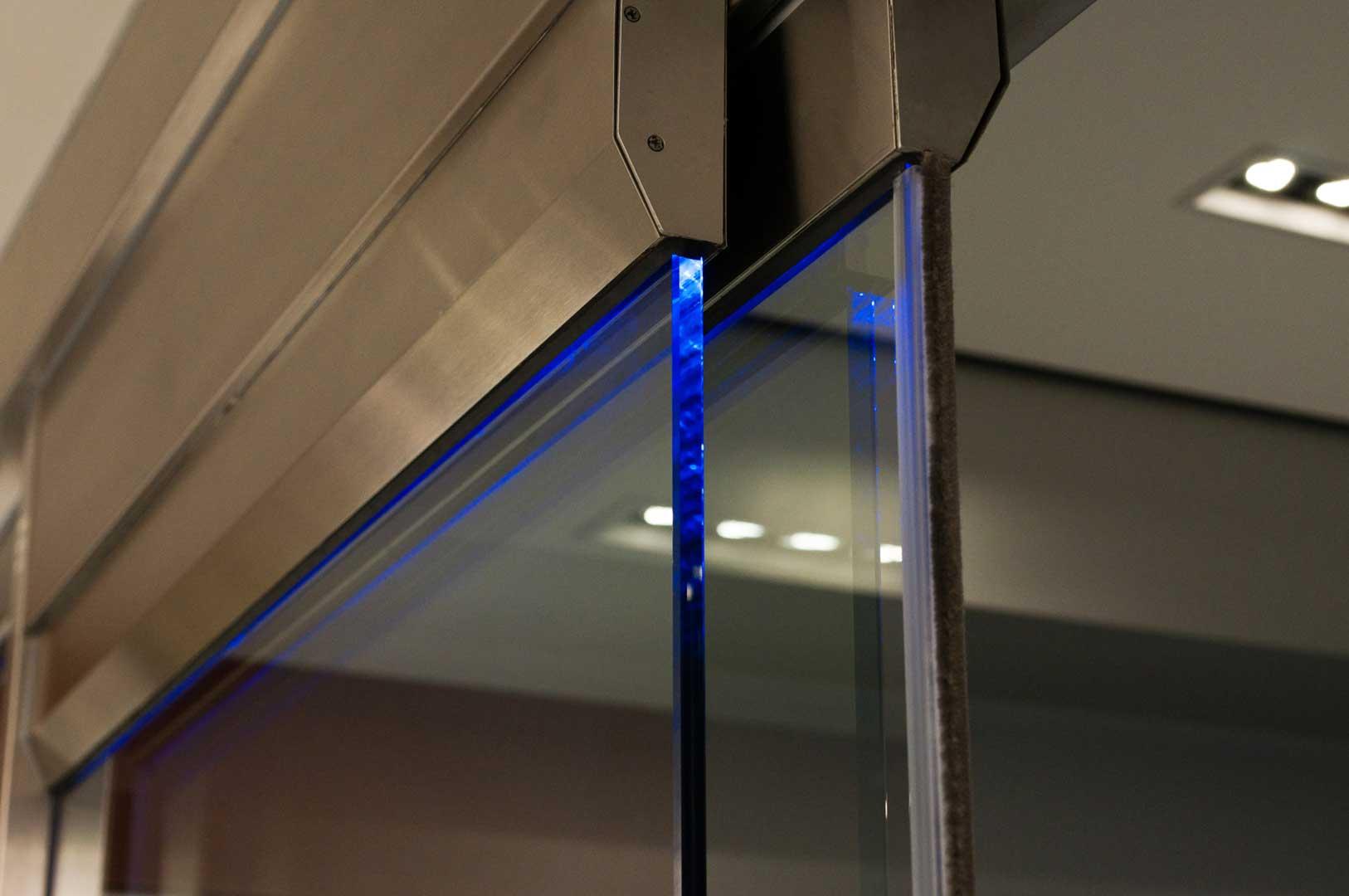 Top Door edge of a Tormax Sliding door system showcasing blue LED lights